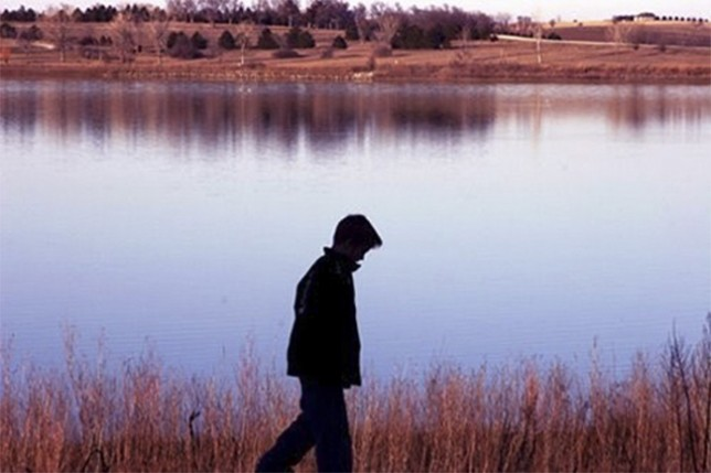 Teen boy beside lake - stress relief tips list