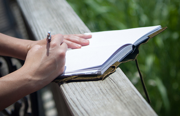 Woman writing in gratitude journal