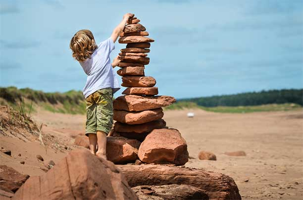 Boy Stacking Stones - Unschooling