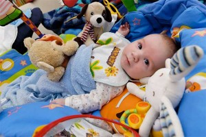 Baby surrounded by toys - creating community: interdependence